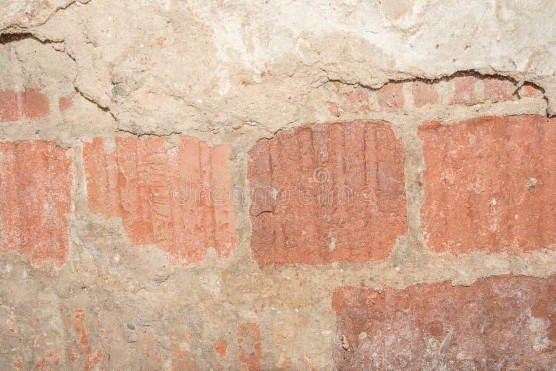 Textur av yttersidan av den gamla väggen av byggnaden, där är brott, sprickor, färgskilsmässor och saltar insättningar royaltyfri bild