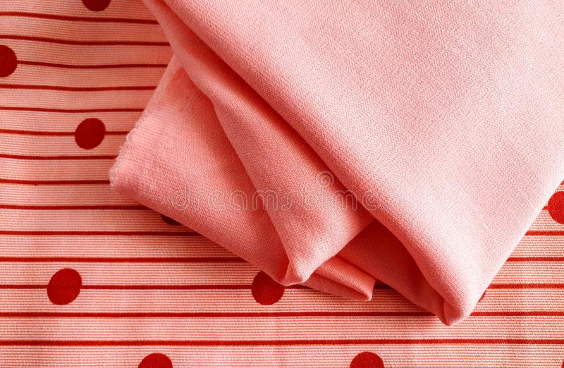 Textur, bakgrund, modellen, beiga eller orange bomull med rödaktiga prickar kombineras med mjuk persikafärgbomull Detta tyg kan royaltyfria bilder