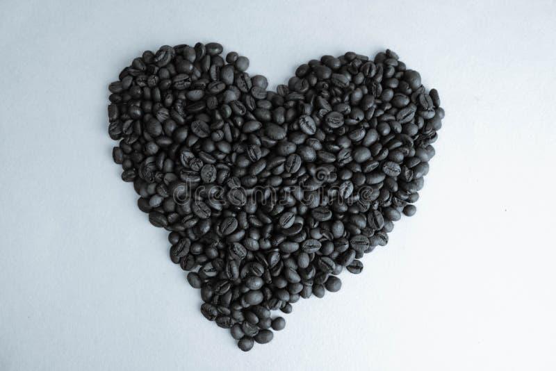 Textur i formen av en hjärta från bönor för grillad utvald läcker genomdränkt brun naturlig doftande Arabica och för Robusta kaff arkivfoto