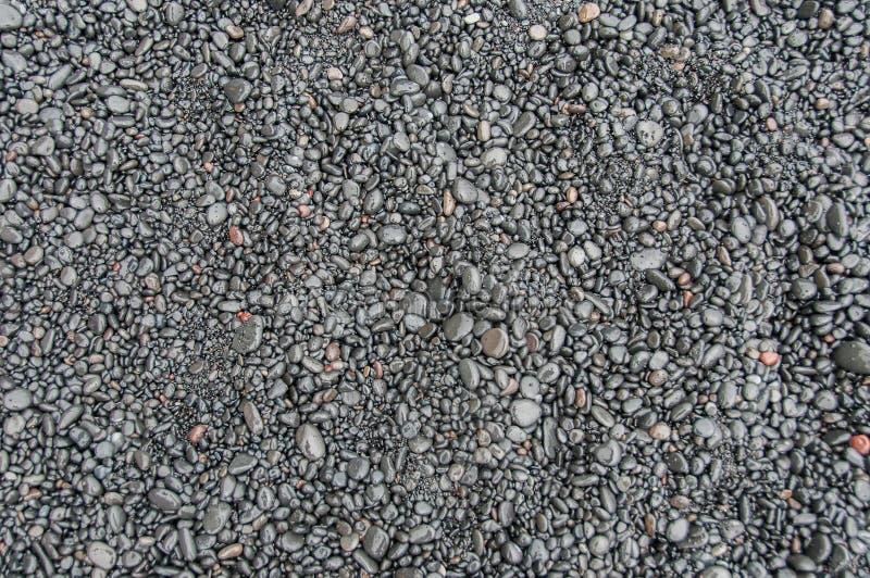 Textur och modellen som skapas av små basaltstenar på en svart sand, sätter på land i Island royaltyfri foto