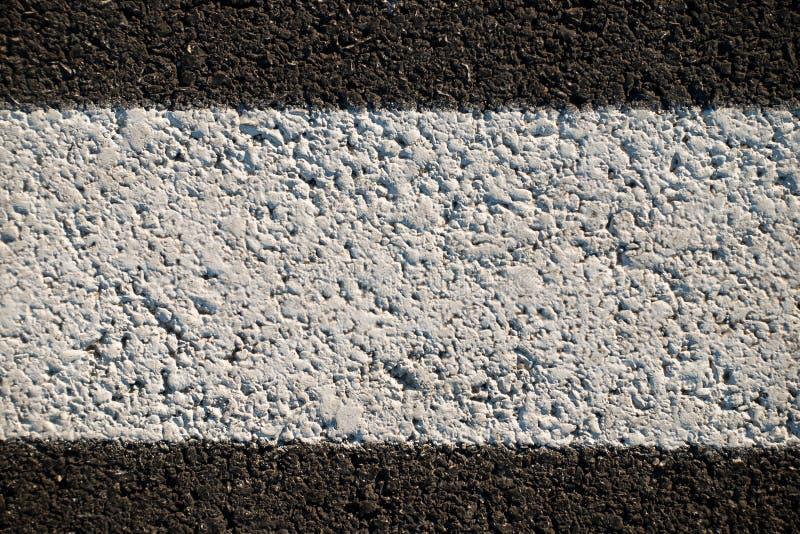 Textura abstrata de uma estrada asfaltada com pintura branca imagem de stock