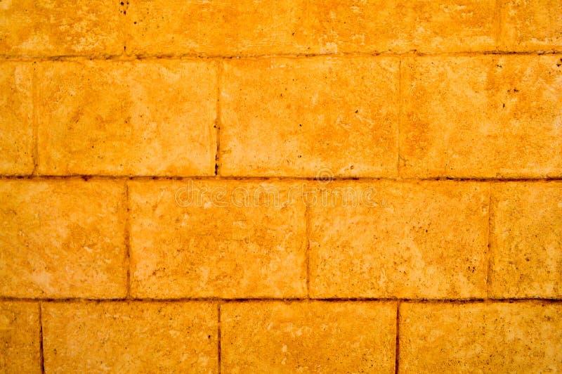 Textura amarela da parede de pedra do tijolo antigo velho com telhas, blocos com emendas fotografia de stock royalty free