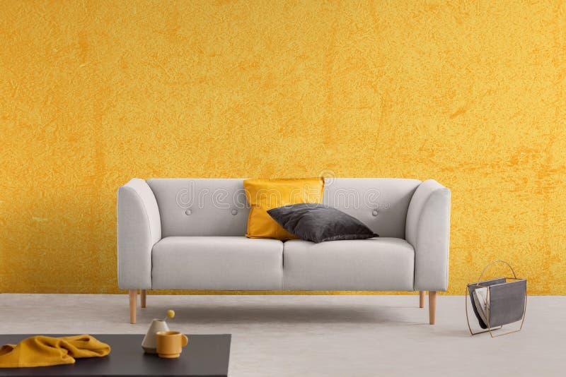 Textura amarilla en la pared y el sofá con las almohadas, foto real con el espacio de la copia foto de archivo libre de regalías