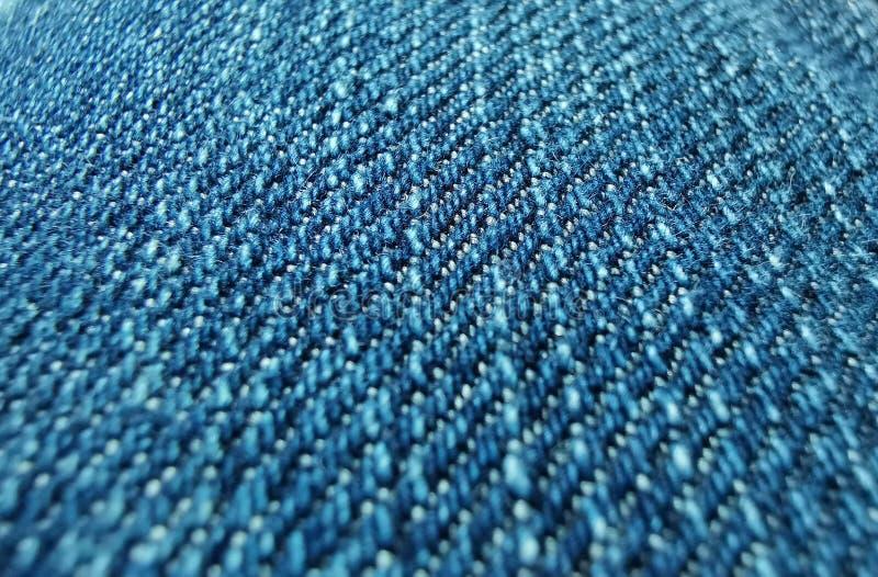 Textura ascendente próxima das calças de brim do fundo de calças de ganga foto de stock