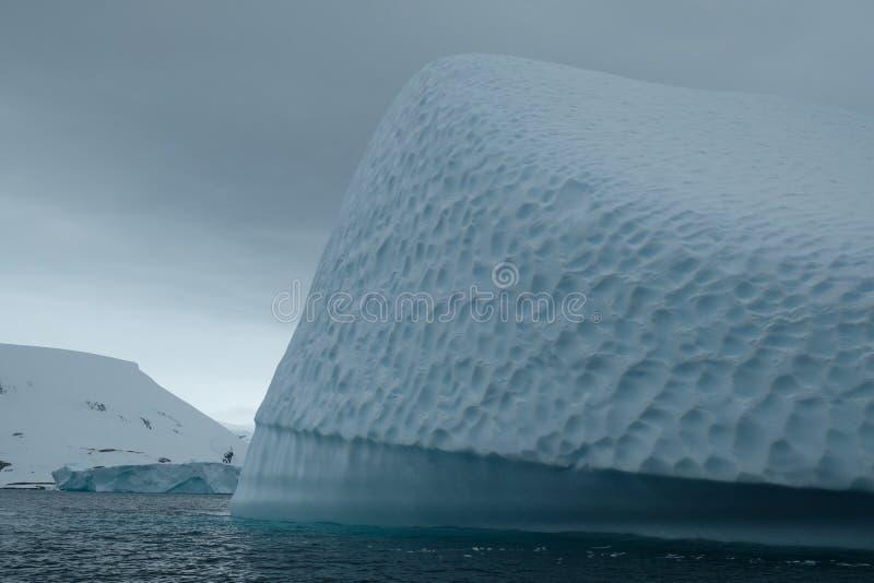 Textura azul original da arte do iceberg da Antártica abaixo do céu nebuloso MONTANHAS NEVADO imagem de stock royalty free