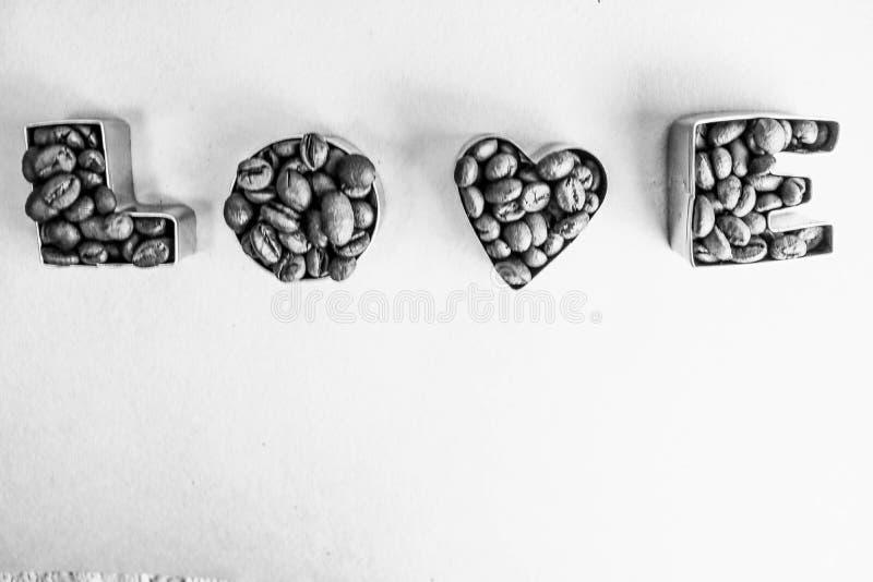 Textura com o amor da palavra para a inscrição do dia de Valentim feita do fundo aromático marrom selecionado dos feijões de café imagens de stock royalty free