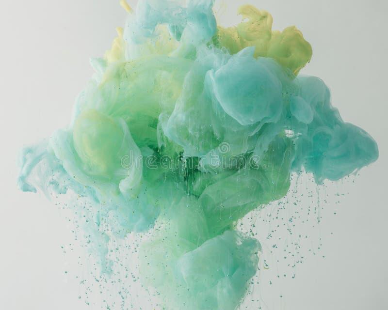 textura con la pintura ligera de la turquesa que fluye en agua con los descensos, aislados en gris fotos de archivo libres de regalías