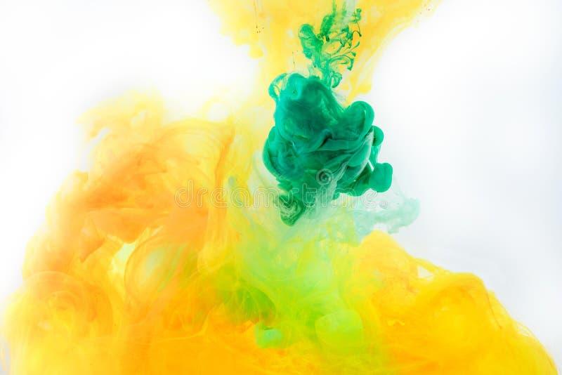 textura con la pintura verde y anaranjada que remolina en agua imagen de archivo