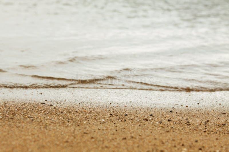 Textura da areia e a água do mar de Yellow Sea, o horizonte entre o mar e a costa, fundo borrado fotos de stock