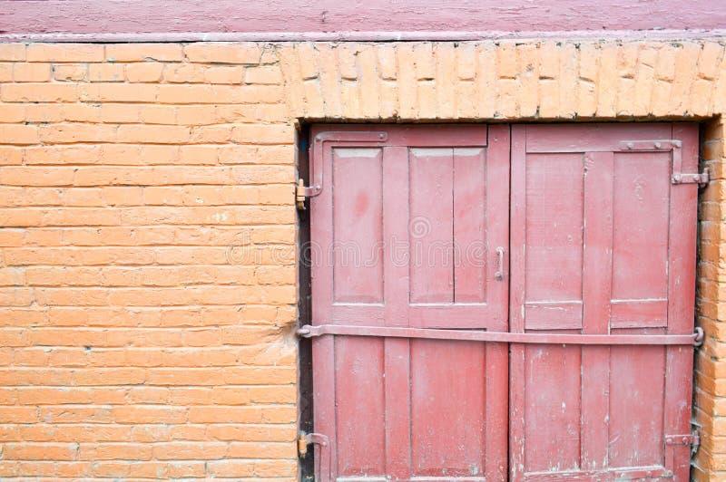 A textura da laranja do tijolo pintou a pintura marrom de uma parede de tijolo velha com emendas e de uma porta de madeira vermel fotografia de stock