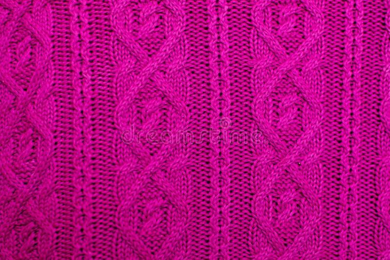 Textura da malha da tela feita malha lãs do rosa com teste padrão do cabo como o fundo Textura magenta imagem de stock royalty free