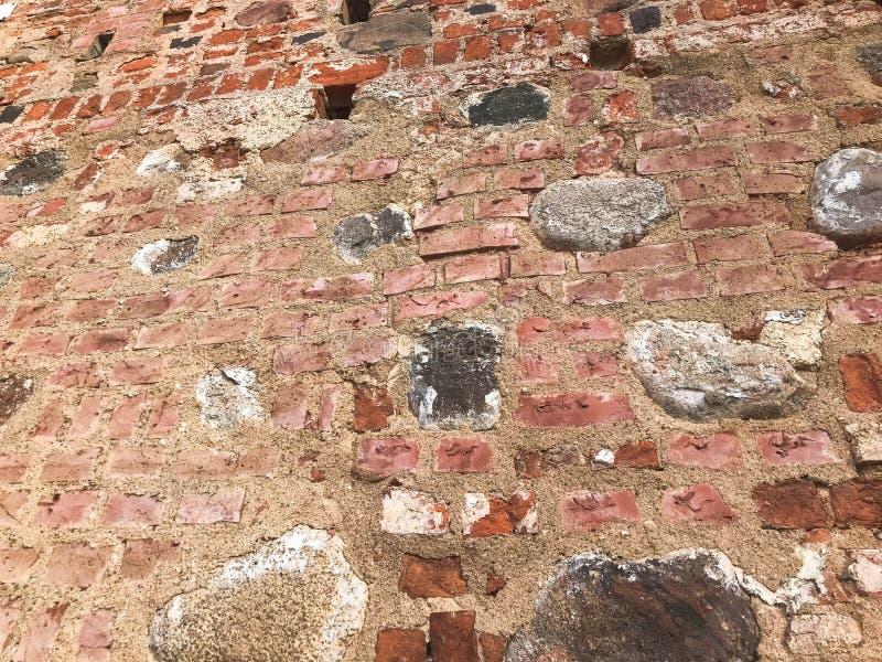A textura da parede de tijolo rachada de descascamento dura da pedra antiga medieval antiga velha de grandes pedras dos tijolos r imagens de stock royalty free
