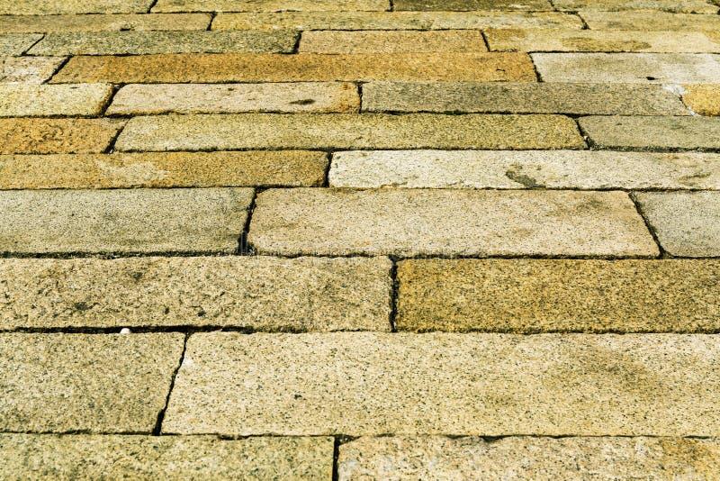 A textura da superfície da pedra velha pavimentou a estrada, fundo da textura do pavimento foto de stock royalty free