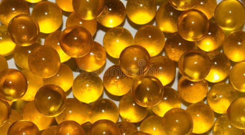 A textura das bolas translúcidas redondas do ouro no fundo branco OVAS dos peixes, óleo de peixes fotografia de stock