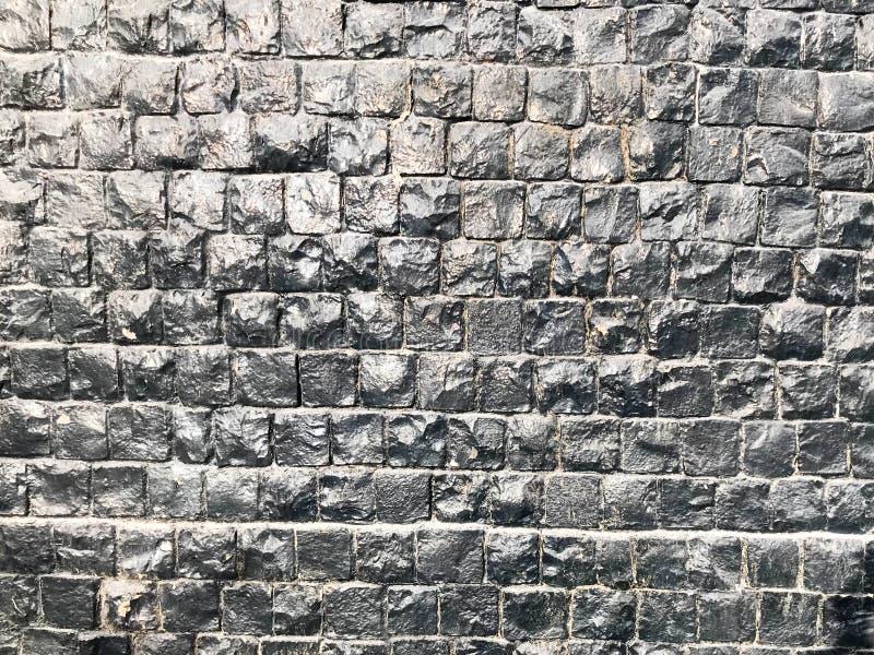 A textura das telhas quadradas pequenas pequenas, paredes de um quadrado apedreja os tijolos do relevo pintados com pintura brilh imagens de stock
