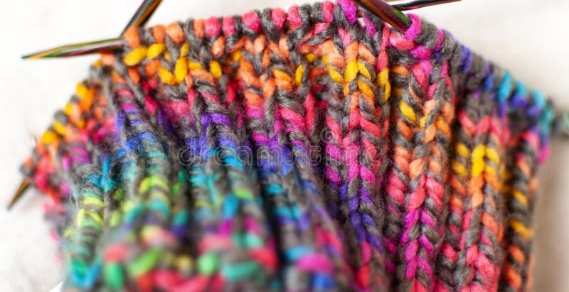 Textura de confecção de malhas do teste padrão, fio colorido brilhante e close-up das agulhas imagens de stock
