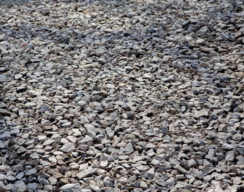 Textura de la grava gris Piso pedregoso gris Una pared de la grava gris Empiedra pequeño y mediano Filos de las piedras Enarene imagen de archivo