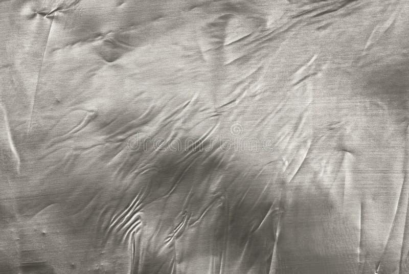 Textura de la hoja de metal gris plateada arrugada con el primer de las abolladuras foto de archivo libre de regalías