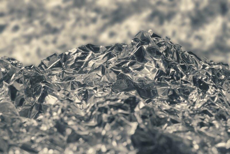 Textura de la hoja de metal gris plateada arrugada con una abolladura bajo la forma de paisaje de la montaña fotos de archivo