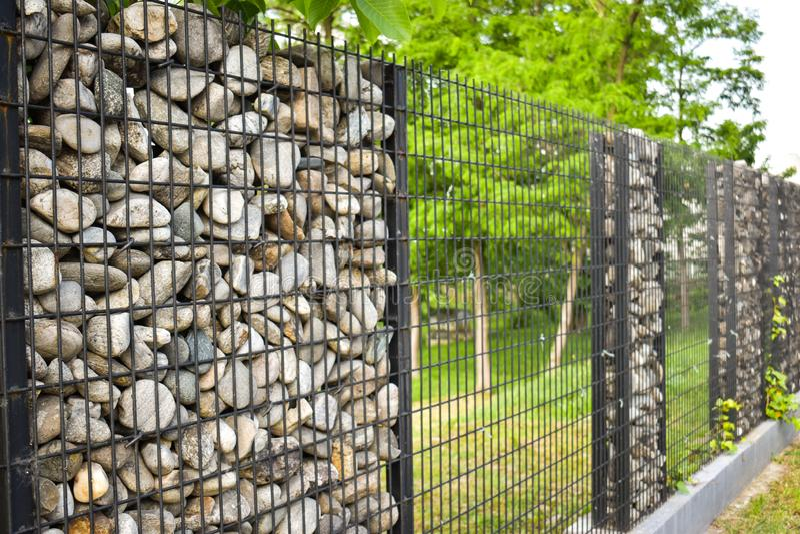 Textura de la pared de piedra La cerca hizo de piedra La pared de piedra se ata alrededor con las barras de acero negras Ideas de imagen de archivo