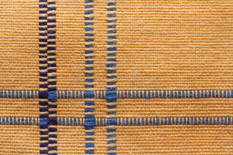 Textura de la tela natural de lino amarilla con las rayas azules. imagen de archivo