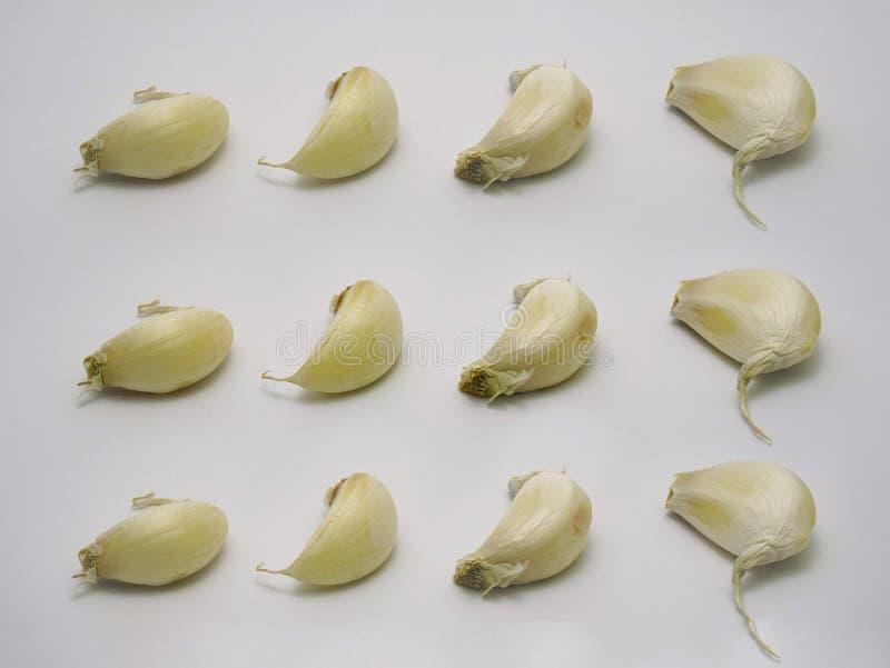 Textura de los clavos de ajo en el fondo blanco, dispuesto en 3 filas y 4 columnas 3 por 4 Un tipo de cocinar el ingrediente imagenes de archivo