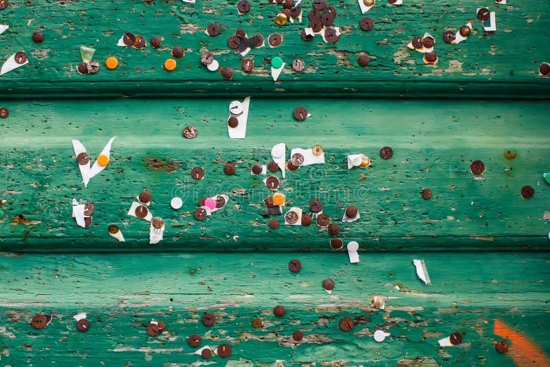 Textura de los tablones de madera del ol verde con las pequeñas hojas de papeles y de pernos oxidados del metal viejo imagenes de archivo