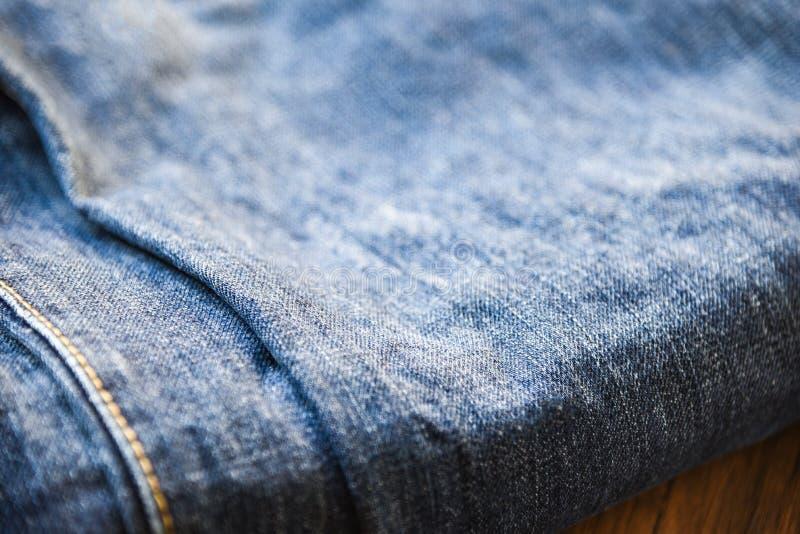 Textura de los vaqueros del dril de algodón de la ropa cerca para arriba del doblez del modelo de los tejanos en fondo de madera  fotografía de archivo libre de regalías