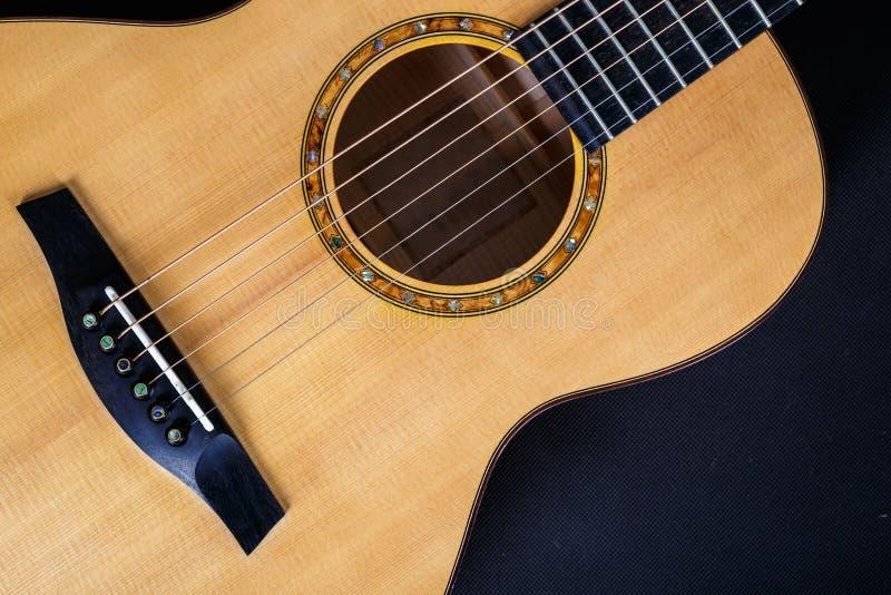 Textura de madeira de uma mais baixa plataforma de seis guitarra acústicas das cordas no fundo preto Forma da guitarra foto de stock royalty free