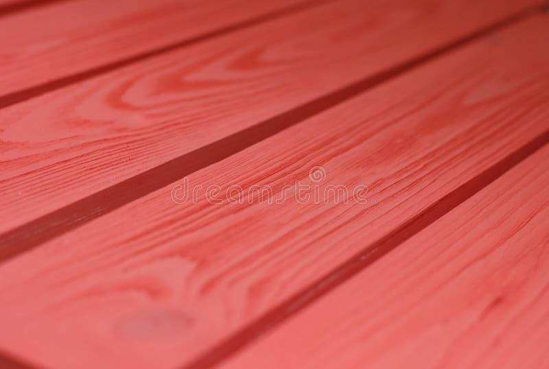 Textura de madera, fondo de madera del grano del tablón del color rojo coral, escritorio en cierre de la perspectiva para arriba, fotografía de archivo
