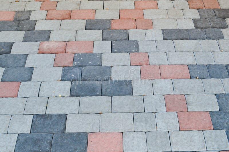 Textura de pavimentos da pedra concreta retangular cinzenta na estrada com emendas O fundo fotos de stock royalty free