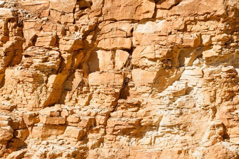 Textura de pedra do fundo Parede amarela da rocha fotografia de stock