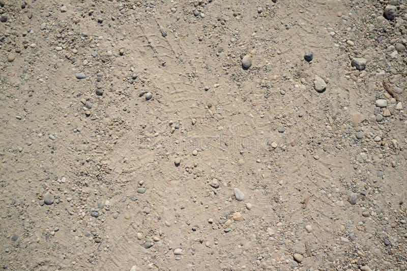 Textura de polvoriento y de Rocky Road con los rastros del coche y de la bicicleta foto de archivo