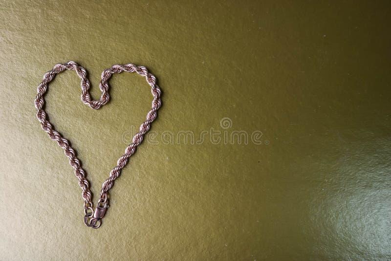 Textura de tejer único de la cadena festiva de oro hermosa en la forma de un corazón en un espacio del fondo y de la copia del or foto de archivo