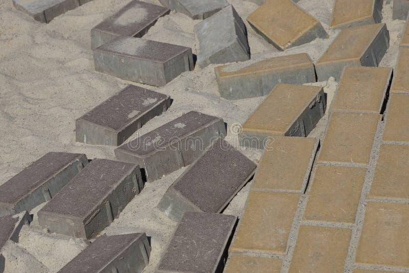 Textura de tijolos de pedra marrons de pavimentos em uma estrada inacabado na areia cinzenta fotos de stock royalty free