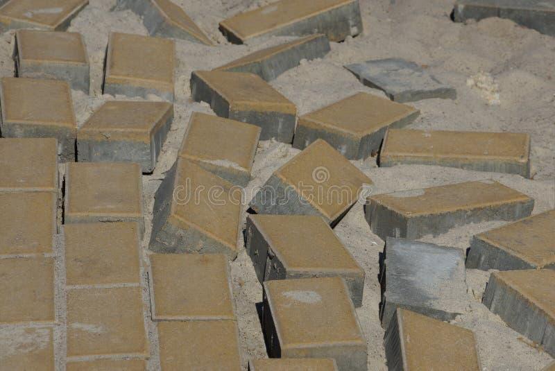 Textura de tijolos de pedra marrons de pavimentos em uma estrada inacabado na areia cinzenta foto de stock