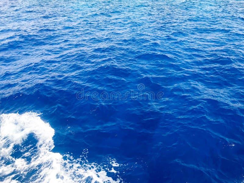 A textura de um mar natural molhado azul fervendo da água pura com ondas, bolhas, espuma branca, espirra, espirra, deixa cair O b fotografia de stock royalty free