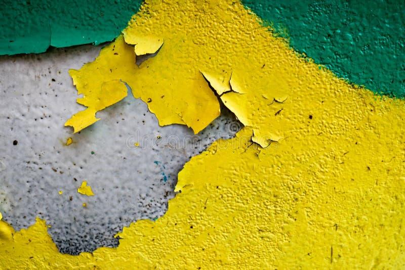 Textura de um muro de cimento gasto velho amarelo e verde de duas cores com pintura varicoloured, poços e testes padrões da casca foto de stock royalty free