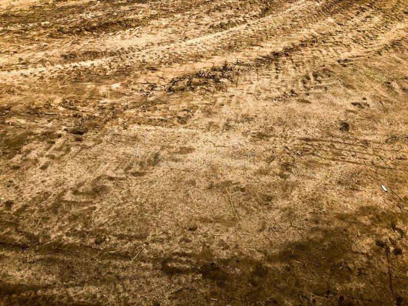 Textura de uma estrada de terra má suja da estrada de terra com poças e de lama de secagem da argila com quebras e rotinas Fora d fotos de stock royalty free