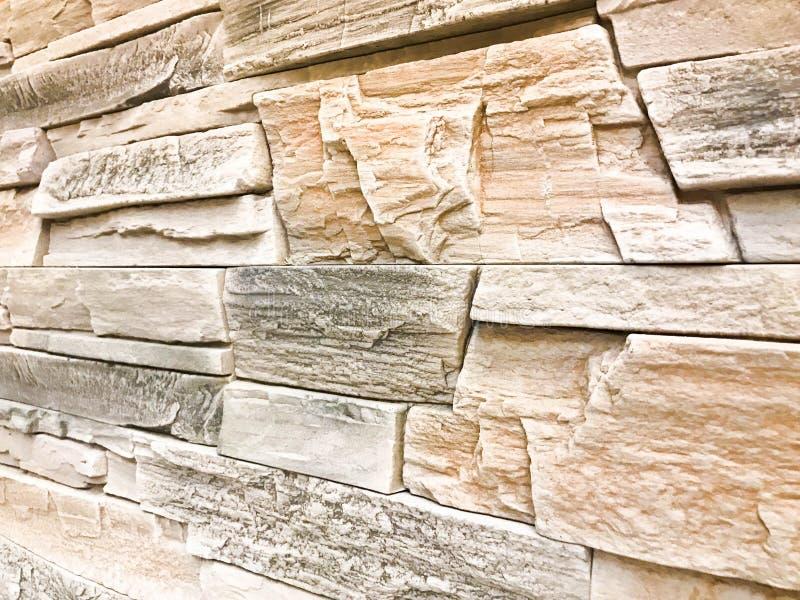 Textura de uma parede da pedra decorativa em um ângulo da pedra textured cinzenta do relevo da construção com emplastro com emend foto de stock