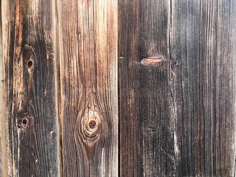 Textura de uma parede de madeira velha cinzenta preta, carbonizada de uma cerca de placas desmedidos idosas verticais de tamanhos foto de stock royalty free