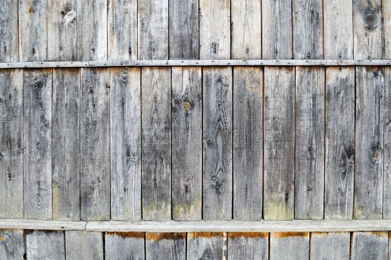 A textura de uma parede de madeira velha cinzenta preta, uma cerca de velho vertical e horizontal embarca rambly de tamanhos dife imagem de stock