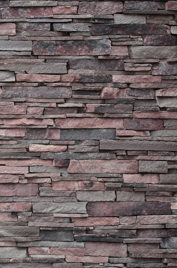 Textura de uma parede de pedra das pedras longas e ásperas de tamanhos e do tom diferentes fotografia de stock