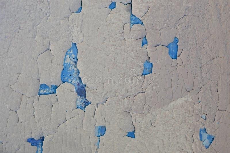 Textura de uma parede rachada cinzenta A pintura velha pode ser vista através das quebras na parede foto de stock royalty free