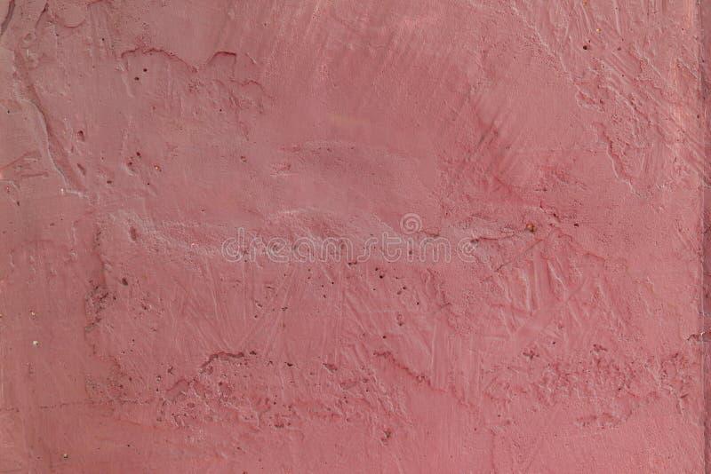 A textura de uma superfície áspera concreta pintada com quebras e furos de uma cor cor-de-rosa interessante foto de stock