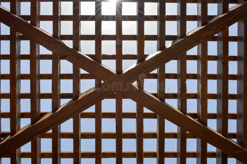 Textura de un enrejado abstracto de madera marrón con las células cuadradas con los agujeros de tableros de haces del registro di foto de archivo libre de regalías