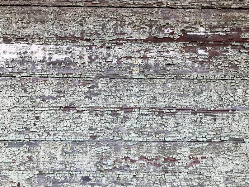 Textura de una pared de madera dilapidada vieja gris negra, una cerca con los pedazos de pintura exfoliated lamentable vieja de r imagenes de archivo