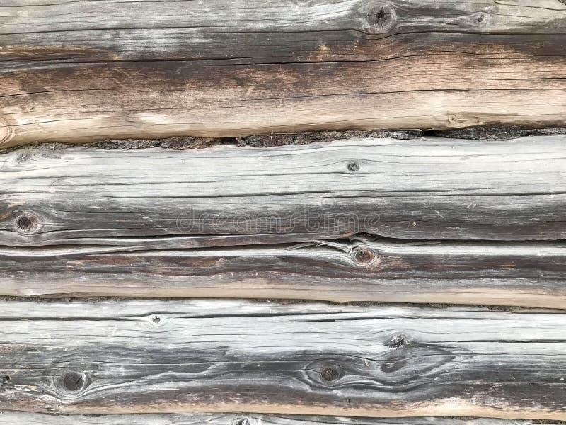 Textura de una pared de madera vieja gris negra hecha de registros, una cerca de tableros gastados con las grietas y de nudos que fotos de archivo libres de regalías