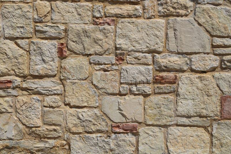 Textura de una pared de piedra Pared de piedra de la casa con el fondo cuadrado de la textura de las tejas Pieza de una cerca de  imágenes de archivo libres de regalías