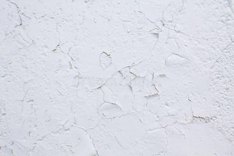 Textura de una pared pintada con la pintura blanca agrietada foto de archivo libre de regalías